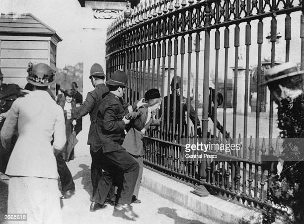 A police officer tries to remove a Suffragette from the railings outside Buckingham Palace during a Suffragette demonstration in London
