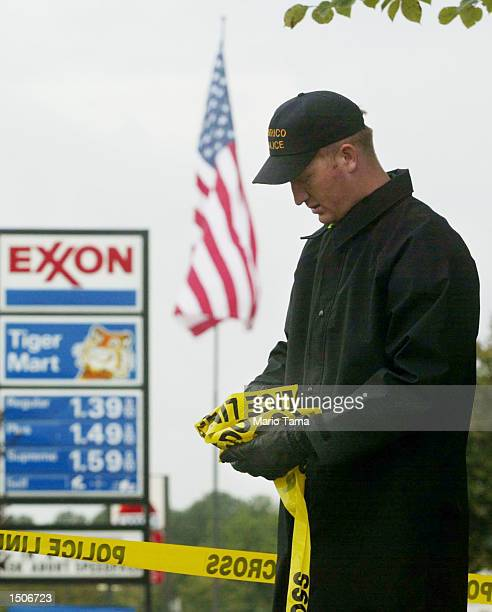 A police officer unfurls crime scene tape at an Exxon gas station where two men in a light van were taken into custody October 21 2002 in Richmond...