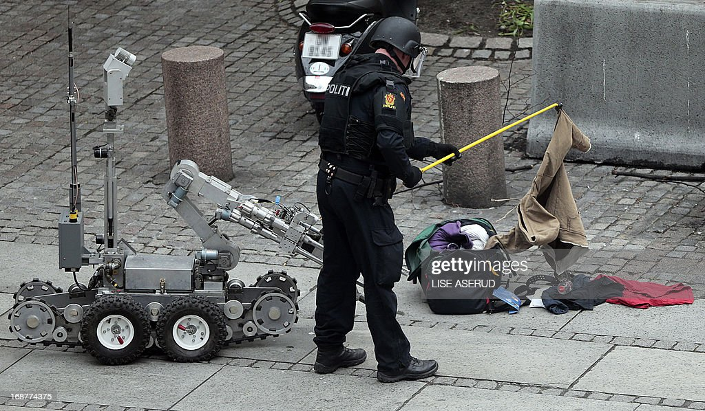 A police officer uses a bombsquad robot to inspect the content of an unidentified bag left in the government area, on May 15, 2013. OUT