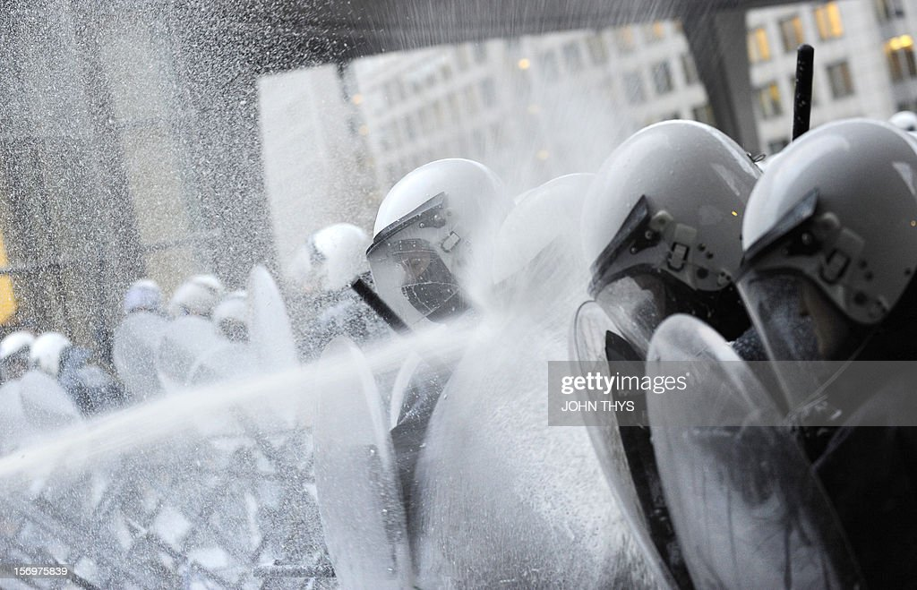 A police officer uses a shield to protect himself from milk being sprayed by dairy farmers, during a protest against European Union agricultural policies, in Brussels, on November 26, 2012. Farmers demonstrated at the European Parliament in Brussels today with tractors and fake cows calling on political leaders to act on falling milk prices caused by overproduction in Europe.