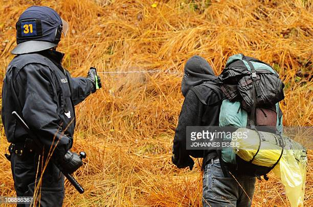 A police officer uses pepper spray on a protestor next to the train tracks on November 7 2010 near in Metzingen near Gorleben Protests are underway...