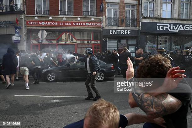 A police officer uses tear gas during clashes with football fans on June 15 2016 in Lille France Football fans from around Europe have descended on...