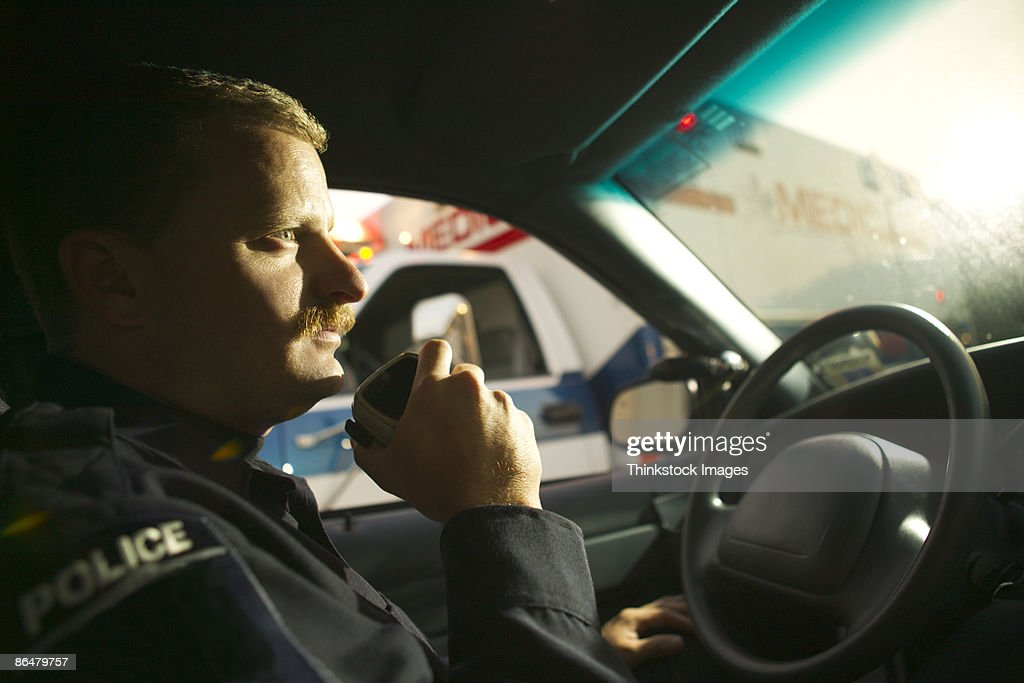 Police officer using radio in car
