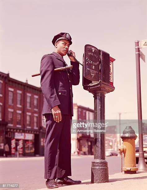 Police officer using telephone at street police callbox. (Photo by H. Armstrong Roberts/Retrofile/Getty Images)