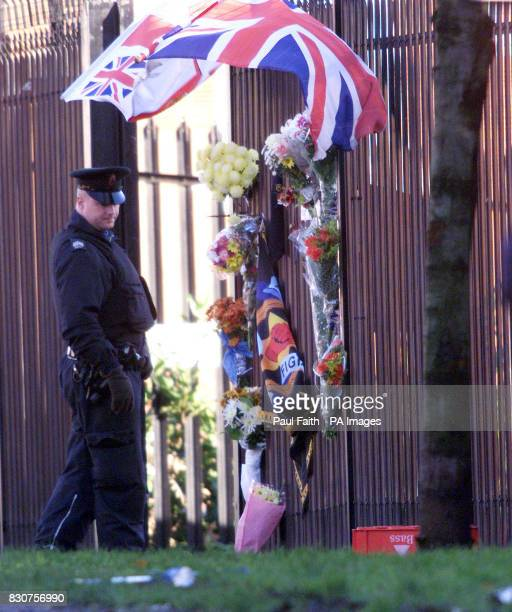 A police officer views flowers laid as a tribute to the 16yearold Protestant youth who was killed last night by a blast bomb he was about to throw...