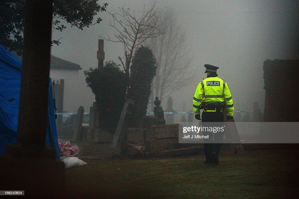 A police officer views the scene as it is confirmed that a grave in Old Monkton cemetery does not contain the body of missing schoolgirl Mora Anderson on January 10, 2013 in Coatbridge,Scotland. Forensic specialist have spent the past three days exhuming the family burial plot of Sinclair Upton, an acquaintance of Alexander Gartshore a former bus driver and convicted rapist linked to the disappearance of Moira.