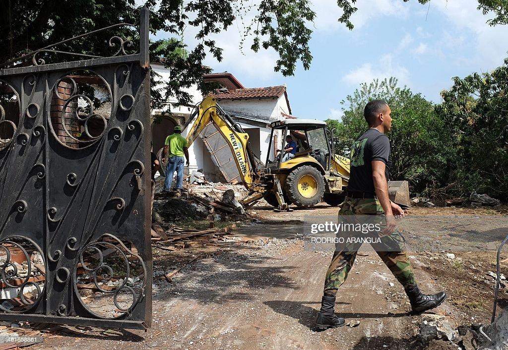 A police officer walks at the residence of Panama's former dictador Manuel Antonio Noriega, currently imprisoned in Panama, Panama City, as it is being demolished on January 9, 2014 following a decision by the Health Ministry for considering it a breeding site of the Aedes mosquito that transmits dengue. Noriega, 79, who was extradited from France in 2011, is serving three 20-year prison terms for the disappearance of opposition activists during his years in power (1983-89). The former dictator has been petitioning to be placed under house arrest since 2012, arguing that his ailing health warrants it. Noriega was toppled from power in a US invasion in 1989, and spent nearly two decades in prison in the United States and France on drug charges. AFP PHOTO/ Rodrigo ARANGUA