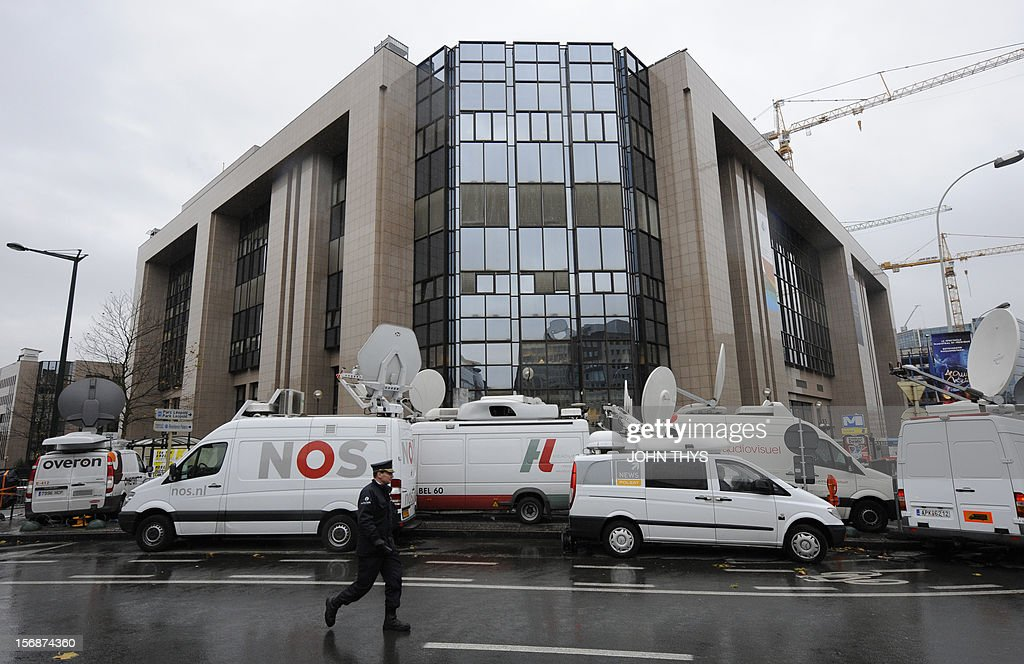 A police officer walks by broadcast trucks parked near the EU Headquarters on November 23, 2012 in Brussels, during a two-day European Union leaders summit called to agree a hotly-contested trillion-euro budget through 2020. European leaders voiced pessimism on reaching a deal on a trillion-euro EU bdget, as gruelling talks pushed into a second day with little prospect of bridging bitter divisions. AFP PHOTO / JOHN THYS