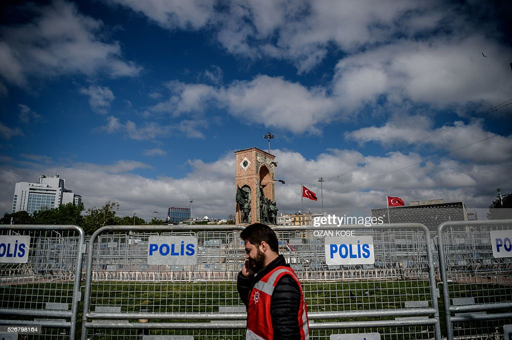 A police officer walks by fences during a May Day rally in Taksim square in Istanbul, on May 1, 2016. Turkish labour activists and leftists marked the annual May Day holiday, with thousands of security deployed and bracing for trouble after the authorities refused to allow protests in central Taksim Square. / AFP / OZAN