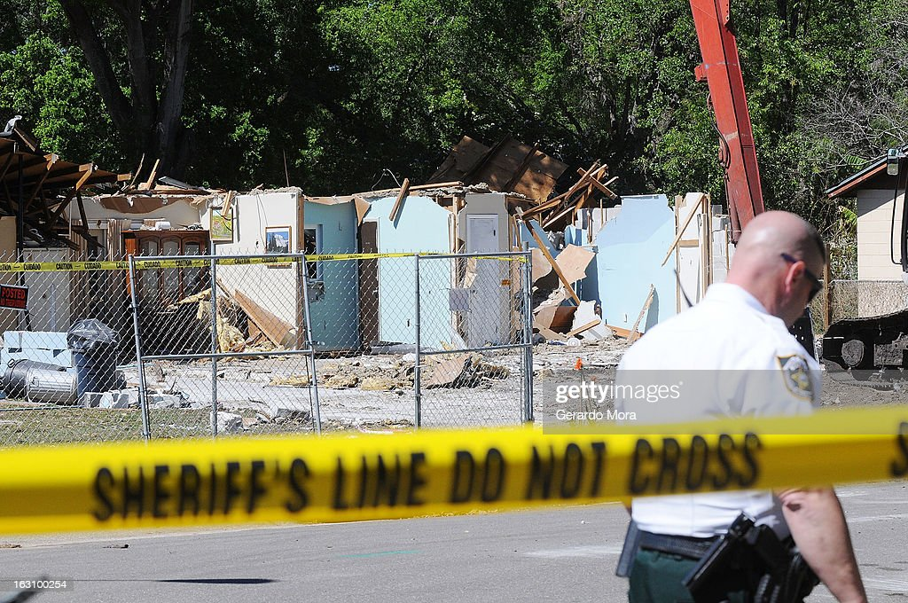 A police officer walks in front of the home where a sinkhole swallowed Jeffrey Bush on March 4, 2013 in Seffner, Florida. Jeff Bush, presumed dead after a sinkhole, estimated at 60 feet deep, opened under his bedroom while he was sleeping in the home. Demolition crews are working to raze the house, recover possessions, and stabilize the now-shaky ground.