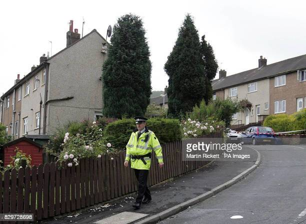 A police officer walks in Hardham Avenue Rawtenstall where a car sits with it's windows smashed opposite the house where an armed man shot a police...