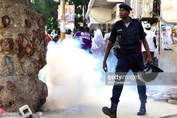 A police officer walks near a cloud of smoke from a tear gas canister as they disperse supporters of the former Senegalese president gathered for an...