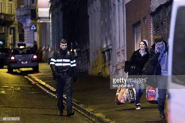 A police officer walks near locals as police set a large security perimeter around 6 Colline street in the city center of Verviers eastern Belgium...