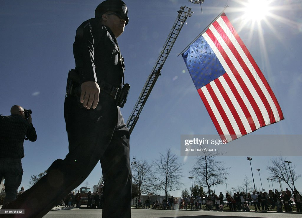 A police officer walks past a flag hanging from a fire truck at the funeral service for Riverside police Officer Michael Crain at Grove Community Church in Riverside, California, February 13, 2013. Officer Crain was allegedly killed by ex LAPD officer Chris Dorner on February 7, 2013.