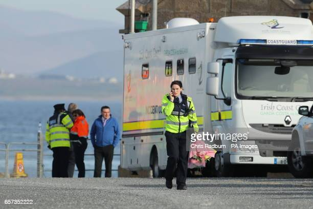 A police officer walks past an Irish Coastguard vehicle with flowers at Blacksod Lighthouse Co Mayo Ireland as dive teams have begun searching the...