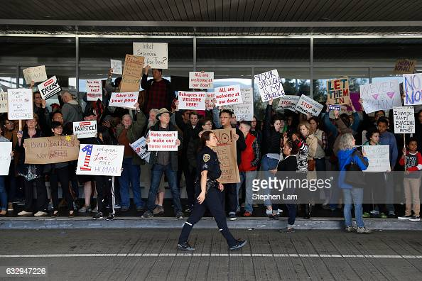 A police officer walks past demonstrators at the international arrival terminal at San Francisco International Airport during a rally against a ban...