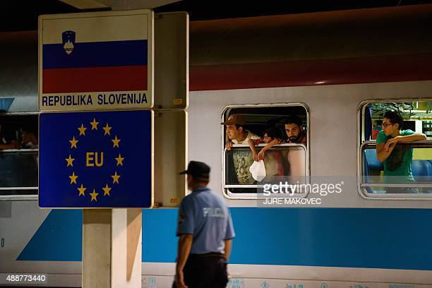 A police officer walks past migrants waiting in a train at the railway station near the SlovenianCroatian border in Dobova Brezice on September 17...