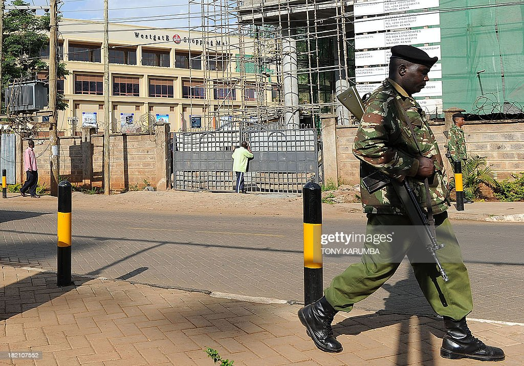A police officer walks past the Westgate mall in Nairobi on September 28, 2013 where forensic experts are still collecting evidence after a deadly four-day siege of the prestigious shopping mall that left close to 70 people dead and more than 60 still missing. Pressure mounted on the Kenyan authorities a week after the Nairobi mall carnage, amid questions over the fate of the missing and accusations Saturday that top brass failed to heed security warnings. President Uhuru Kenyatta has vowed not to bow to the Shebab group that claimed the Westgate mall bloodbath and threatened more attacks if Kenya failed to pull its troops out of Somalia. AFP PHOTO/Tony KARUMBA