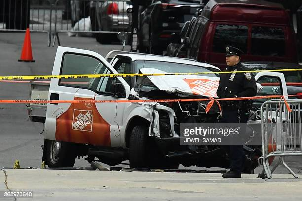 A police officer walks past the wreckage of a Home Depot pickup truck a day after it was used in a terror attack in New York on November 1 2017 The...