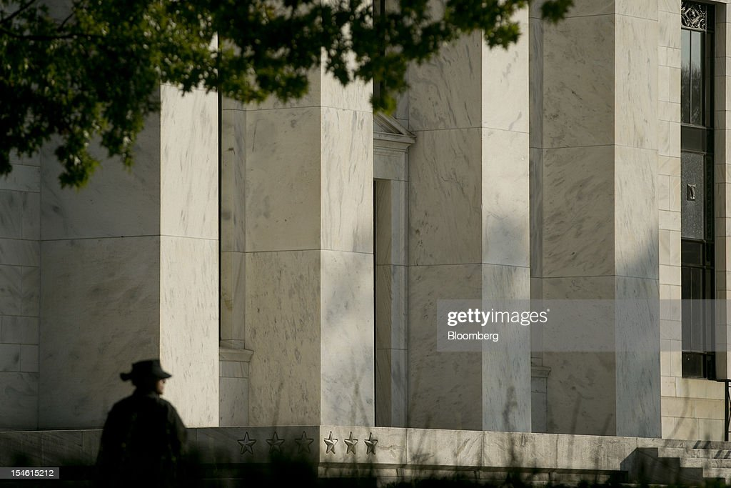 A police officer walks the perimeter of the Marriner S. Eccles Federal Reserve building in Washington, D.C., U.S., on Tuesday, Oct. 23, 2012. Federal Reserve Chairman Ben S. Bernanke, who is seeking to spur the economy with a third round of so-called quantitative easing, has said his stimulus works by lowering borrowing costs and encouraging investors to seek higher-yielding assets. Photographer: Andrew Harrer/Bloomberg via Getty Images