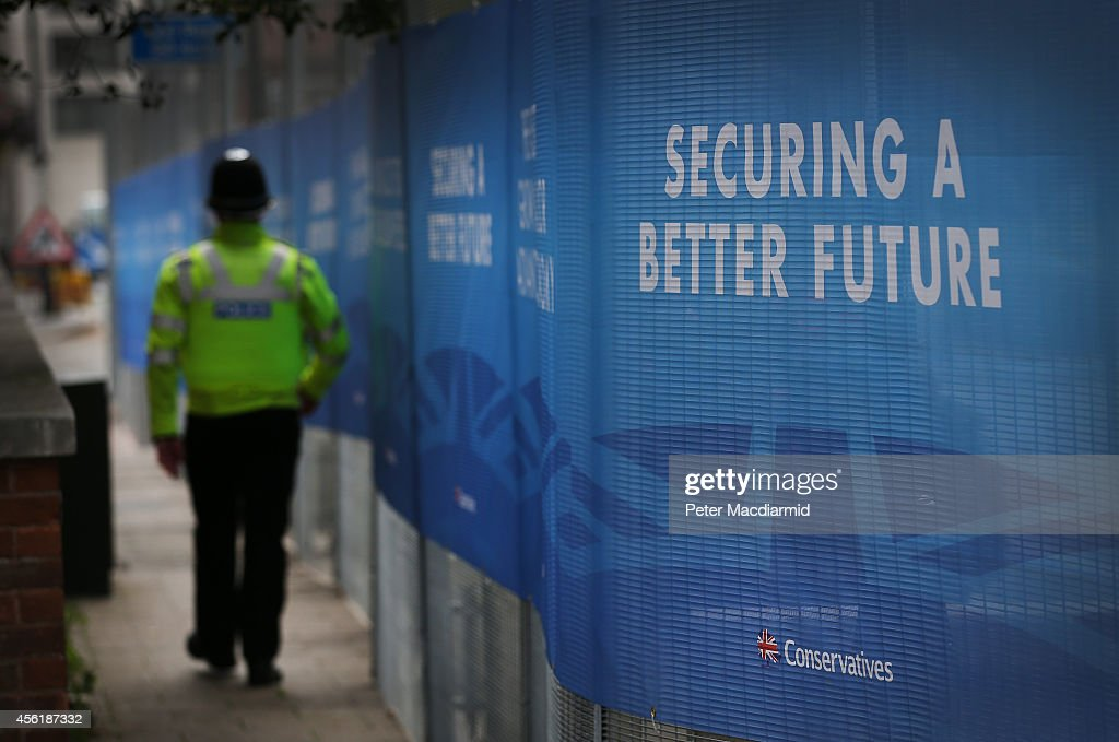 A police officer walks the perimiter fence at the International Convention Centre ahead of the Conservative party conference on September 27 2014 in...