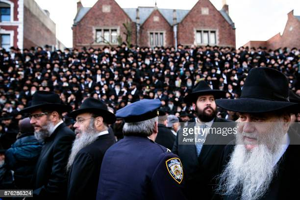 A police officer walks through the crowd as Hasidic rabbis prepare to pose a group photo part of the annual International Conference of...