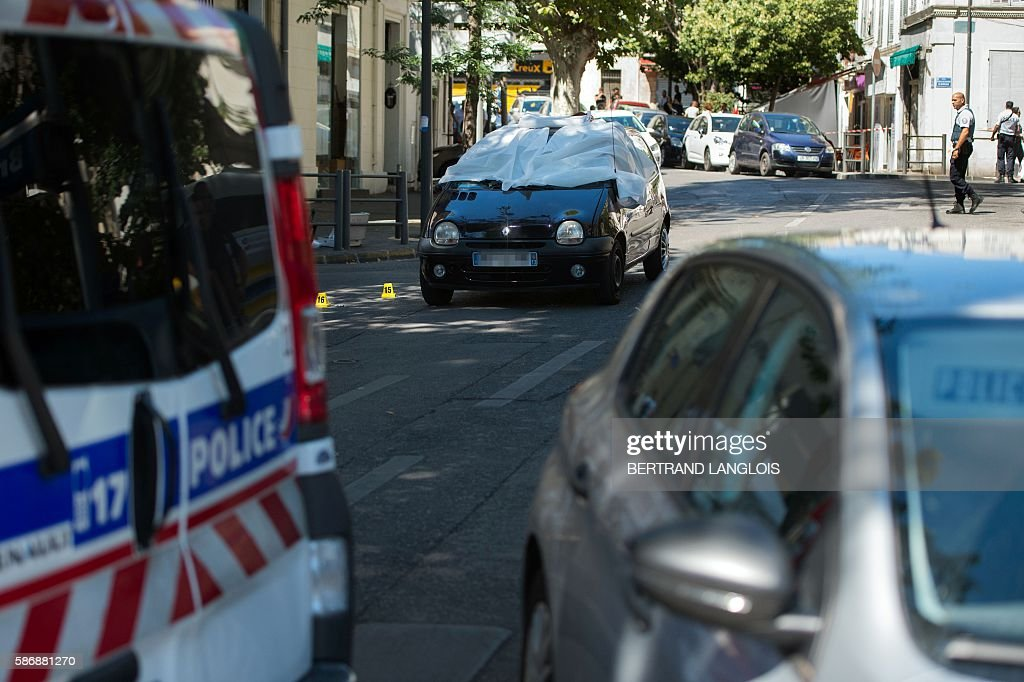 A police officer walks toward the car where two men in their twenties were shot dead near the train station SaintCharles in Marseille southern France...