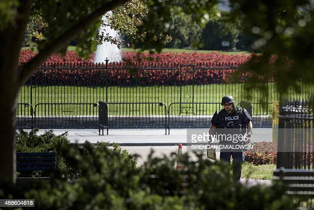 A police officer walks with equipment to check a suspicious package in Lafayette Park in front of the White House September 16 2015 in Washington DC...