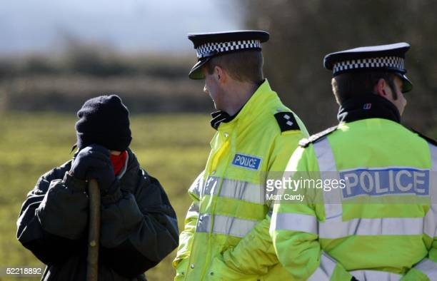 A police officer watches a hunt sabatuer at the start of the Avon Vale Hunt at Monk's Park on February 19 2005 near Corsham Wiltshire England Some...