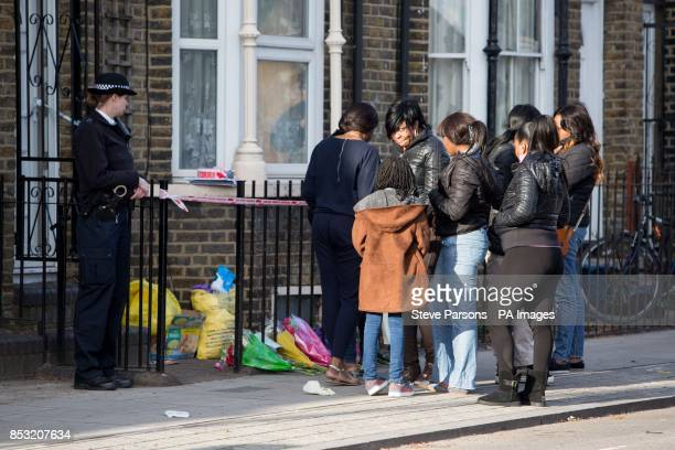 A police officer watches as a group of people gather at the scene in Eastway Hackney east London where a teenage girl named as Shereka Marsh died...