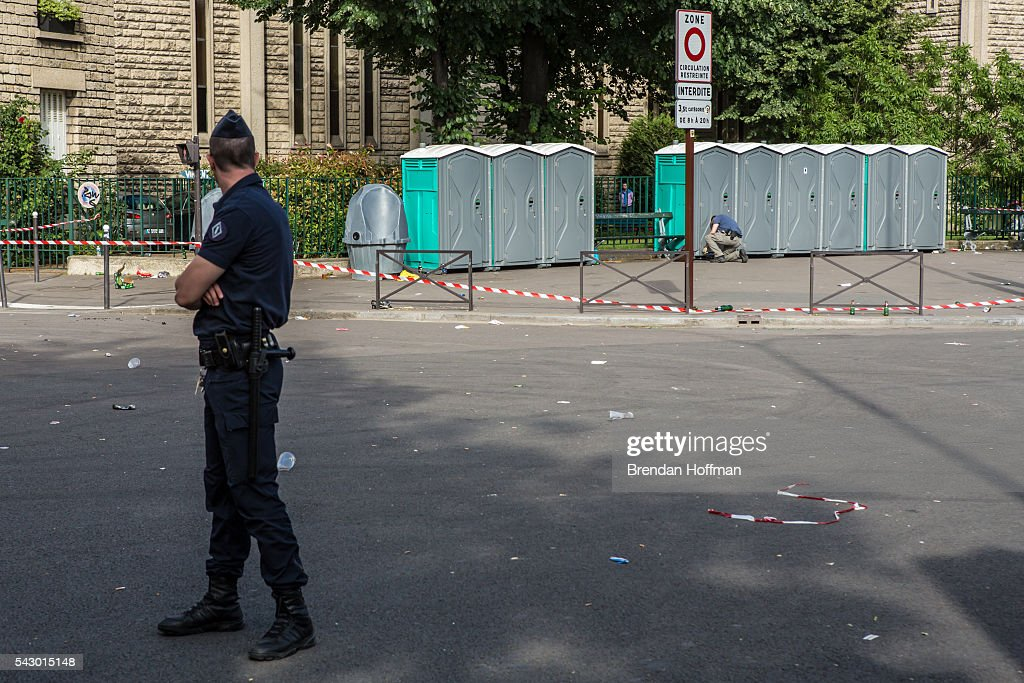 A police officer watches as a man checks portable toilets, suspected of holding a possible bomb, near the Parc des Princes stadium during the football match between Wales and Northern Ireland during UEFA Euro 2016 tournament on June 25, 2016 in Paris, France. There was no bomb. The two teams met in the Round of 16 at Parc des Princes in Paris, where Wales won 1-0.