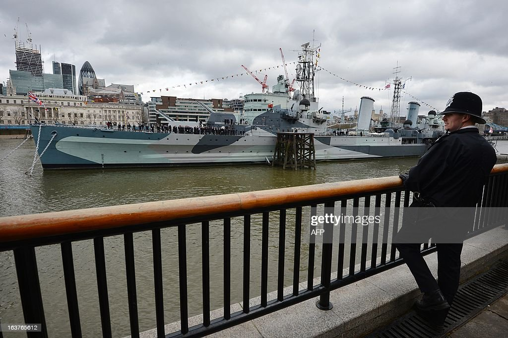 A police officer watches as HMS Belfast sails past during a ceremony marking its 75 anniversary in London on March 15, 2013. HMS Belfast is a large light cruiser of the Town-class which saw action in the Second World War and the Far East 1946-1950 and is now a museum ship moored on the River Thames just in front of Tower Bridge. HMS Belfast was launched on March 17, 1938 and was decommissioned in 1965 becoming part of the Imperial War Museum in 1978. The ship celerbates this year in 2013 its 75th anniversary.