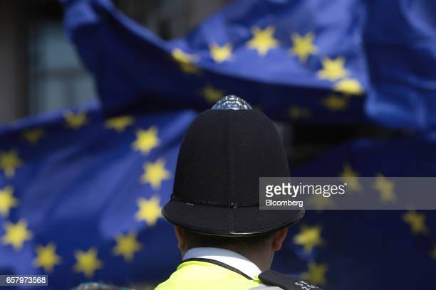 A police officer watches as protesters wave European Union flags during a Unite for Europe march to protest Brexit in central London UK on Saturday...