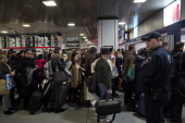A police officer watches as travelers wait to board Amtrak trains at Penn Station in New York US on Wednesday Nov 27 2013 Heavy rain will fall today...