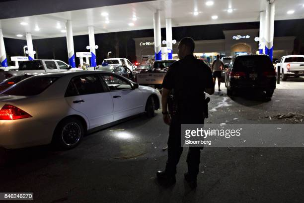 A police officer watches motorists at a Marathon gas station after announcing the stations closing due to a county wide curfew in Estero Florida US...