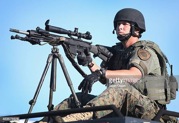 A police officer watches over demonstrators protesting the shooting death of teenager Michael Brown on August 13 2014 in Ferguson Missouri Brown was...