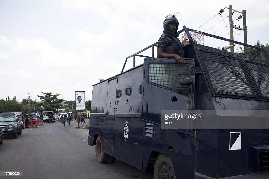 A police officer watches protesters angry over alleged vote-rigging on December 8, 2012. in Accra.Ghanaian authorities fired tear gas on Saturday to disperse a crowd of more than 100 people in the capital Accra who were angry over rumours of rigging in the country's elections. AFP PHOTO