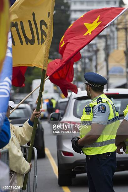 A police officer watches protesters outside Premiere House as New Zealand's Prime Minister John Key and China's President Xi Jinping hold a joint...