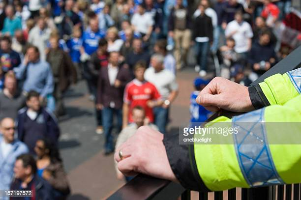Police officer watching over football fans crowd