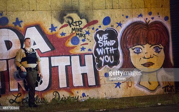A police officer wathches demonstrators marking the oneyear anniversary of the shooting of Michael Brown protest along West Florrisant Street on...