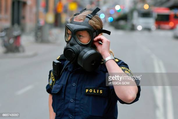 A Police officer wearing a gas mask works at the scene where a truck crashed into the Ahlens department store at Drottninggatan in central Stockholm...