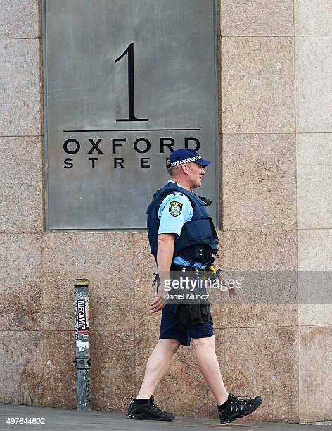 Police officer wearing a life vests walks next to 1 Oxford Street building on November 18 2015 in Sydney Australia Armed police stormed the office...