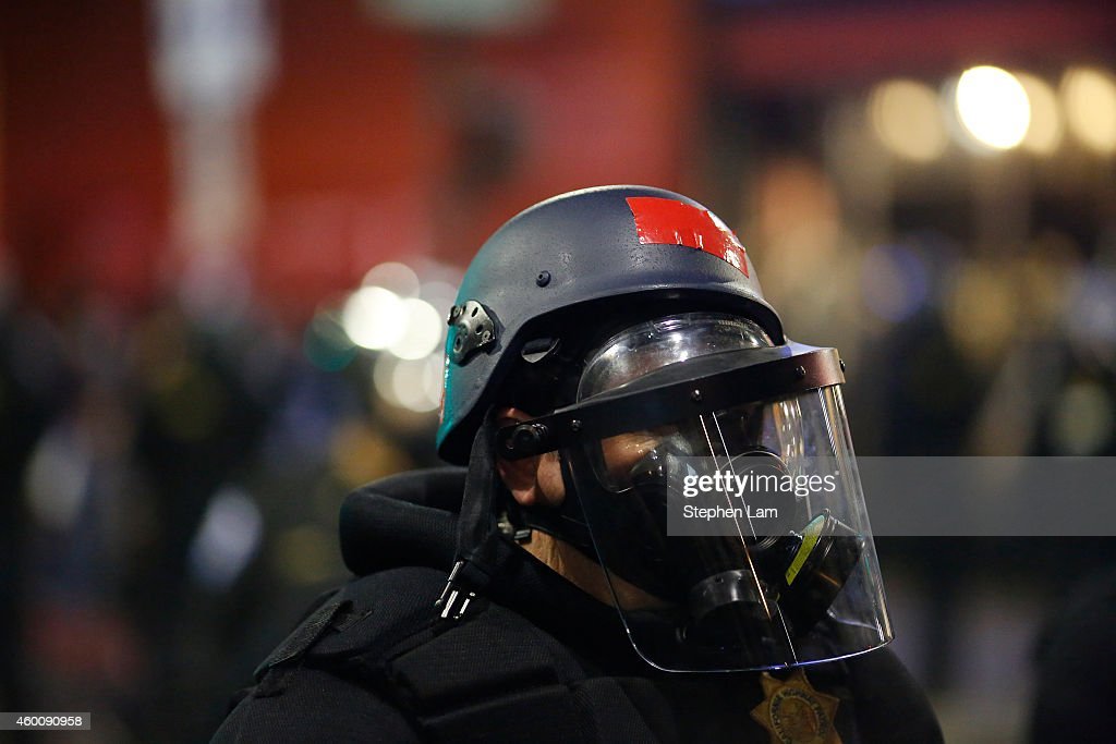 A police officer with a broken visor stands in a line on Telegraph Ave during a demonstration over recent grand jury decisions in policeinvolved...