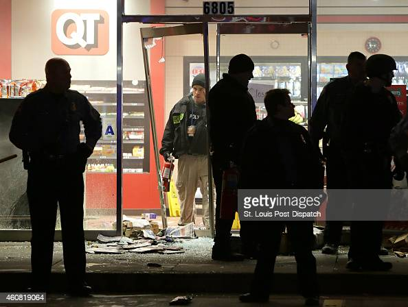 A police officer with a fire extinguisher stands in the broken out entry to a QuikTrip that was partially looted and set on fire on Wednesday Dec 24...