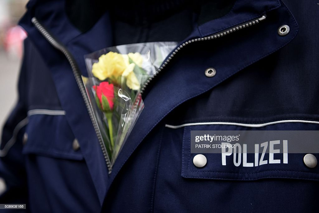 A Police officer with flowers stands next to revellers near the central station on February 7, 2016 in Cologne, western Germany. Germany's carnival season is underway with increased security in Cologne, a city rocked by a rash of reported sexual assaults blamed on migrants. / AFP / PATRIK STOLLARZ