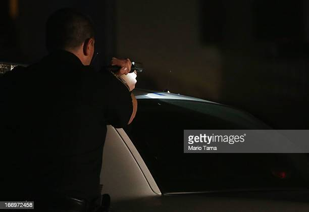 A police officer with gun drawn and flashlight searches for a suspect on April 19 2013 in Watertown Massachusetts Earlier a Massachusetts Institute...