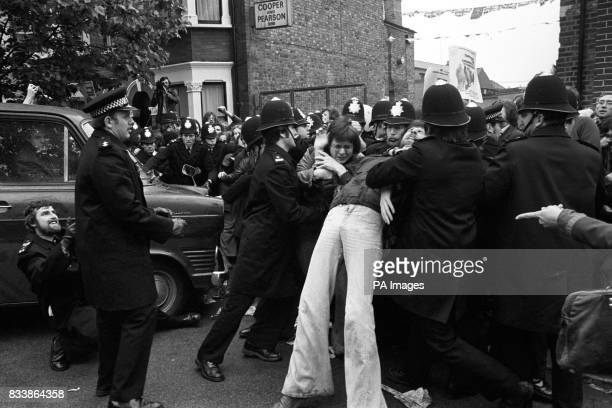 A police officer with his foot trapped under a van appeals for help as his colleague get to grips with pickets outside the Grunwick processing...