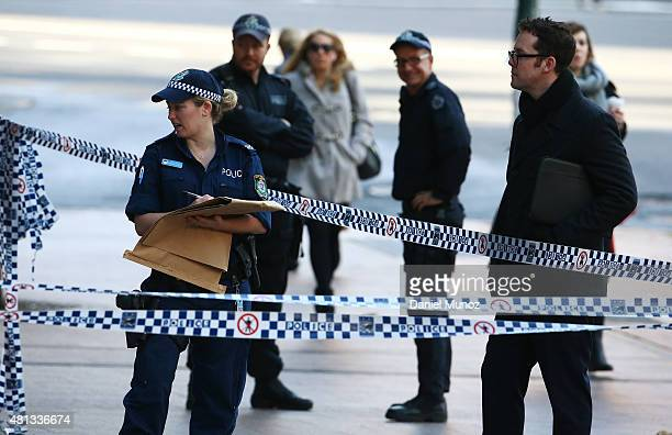 Police officer works at the Australian Federal Police headquarters cordoned with police tape due to a suspicious package on July 20 2015 in Sydney...
