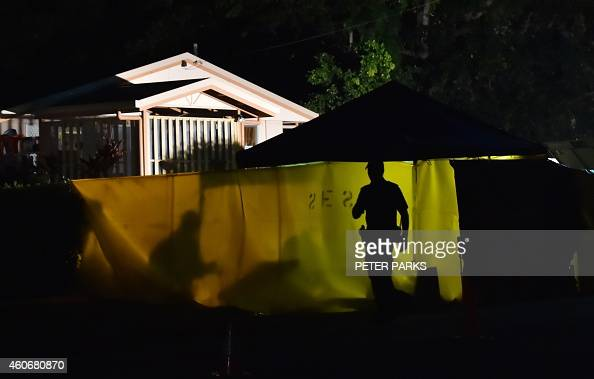 A Police officer works at the scene where eight children ranging from babies to teenagers were found dead in a house in the northern Australian city...