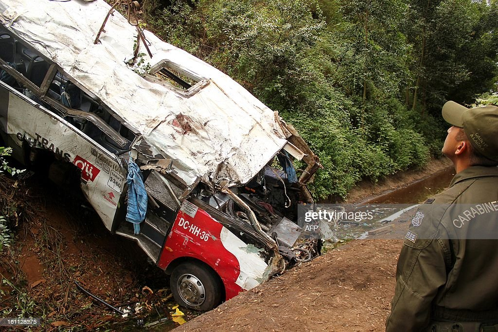 A police officer works at the site of a bus accident near Tome, in Biobio province, some 500 km south of Santiago, on February 9,2013. At least 15 people were killed and 19 others were injured when the bus full of passengers fell into a ravine in central Chile, a local official said.